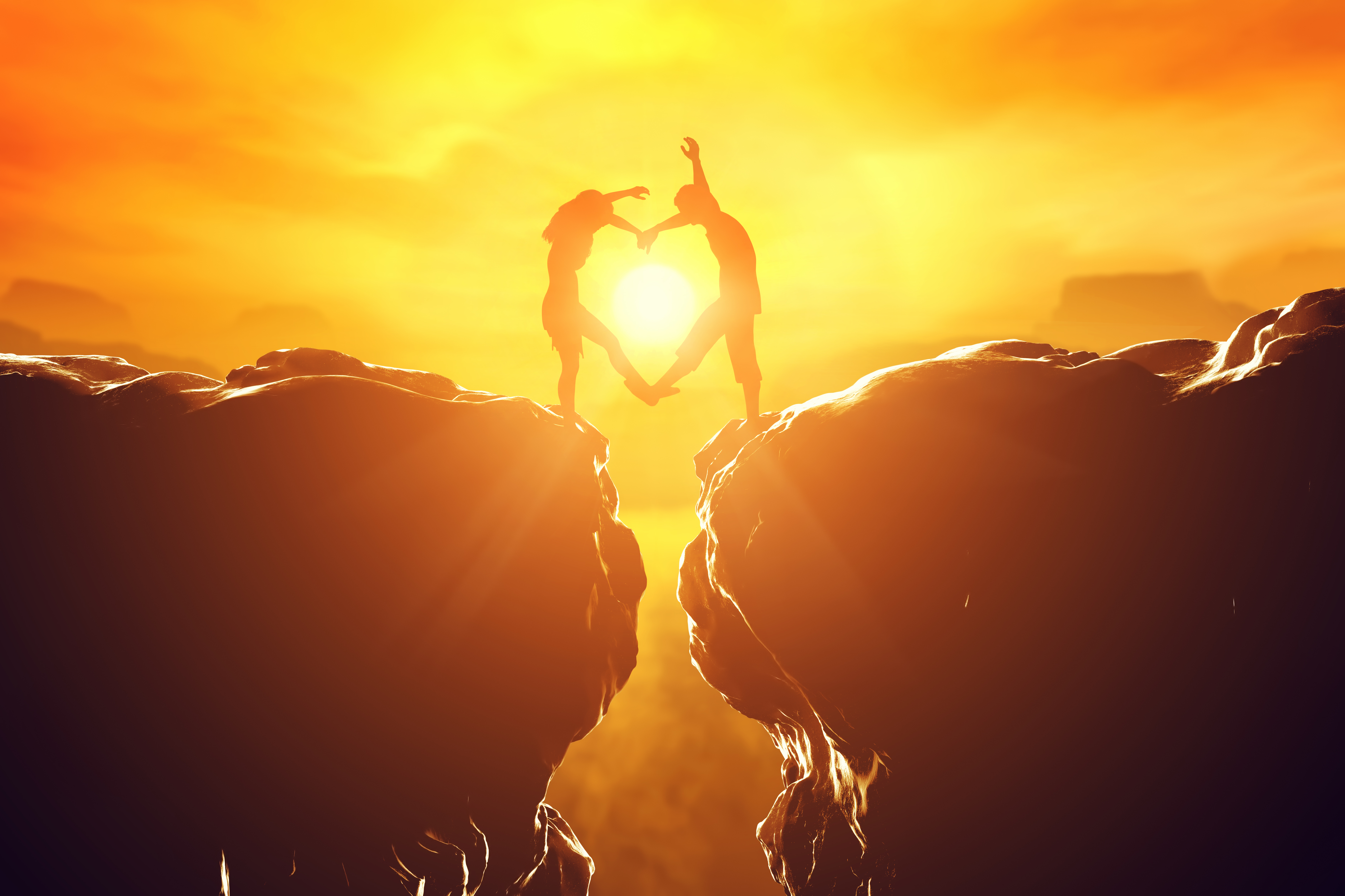 Happy couple making heart shape over precipice between two rocky